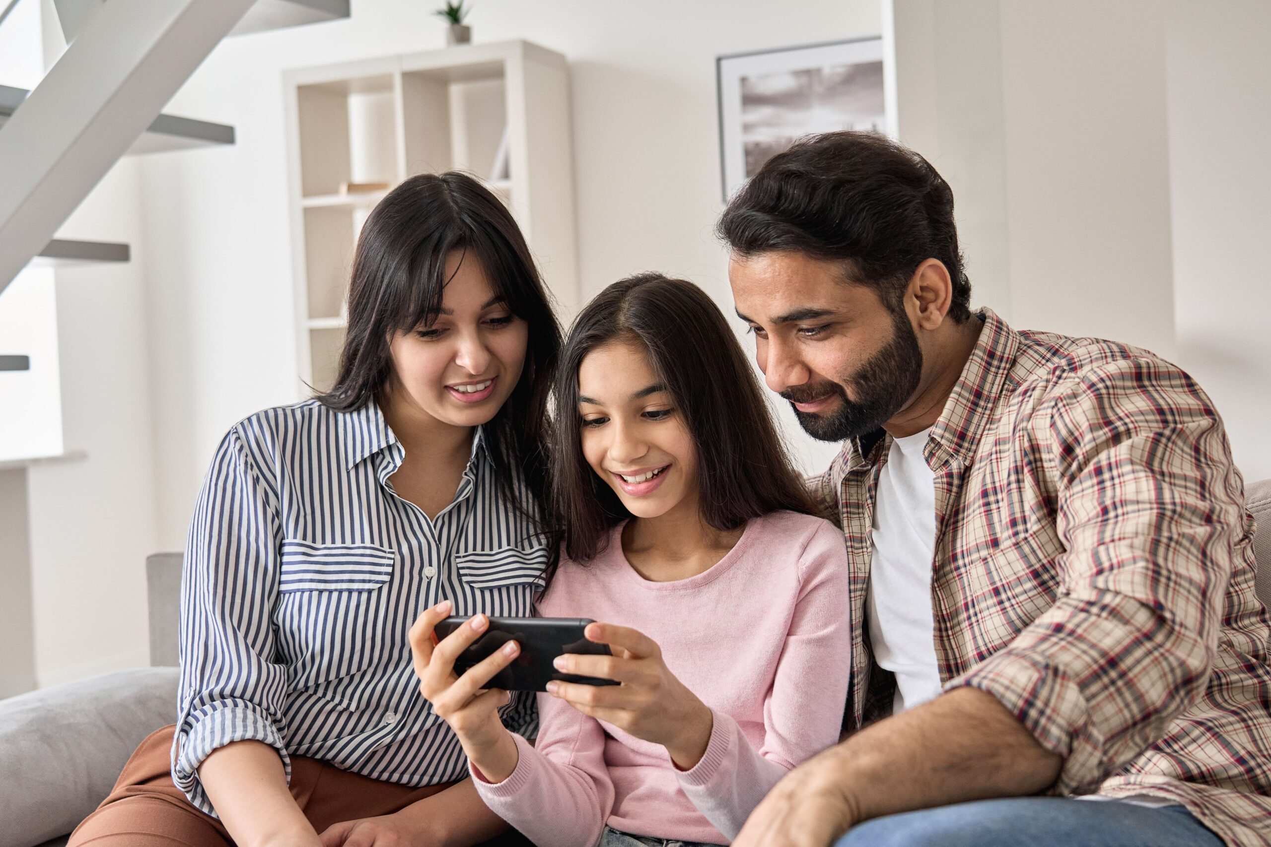 happy-indian-family-and-teen-daughter-using-smart